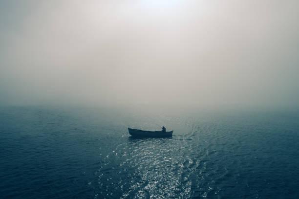 Fischerboot und Fischer im Meer, nebligmorgen über dem Wasser. – Foto