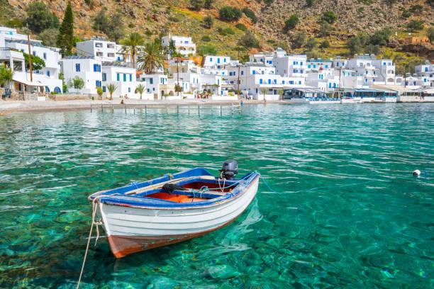 fishing boat and the scenic village of loutro in crete, greece - grecja zdjęcia i obrazy z banku zdjęć