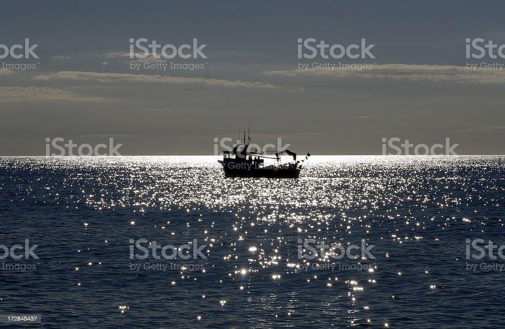 Fishing boat at sunrise. stock photo