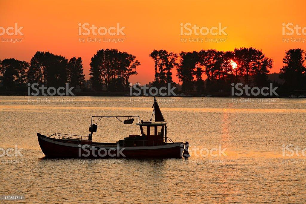 Pesca en bote en la puesta de sol foto de stock libre de derechos