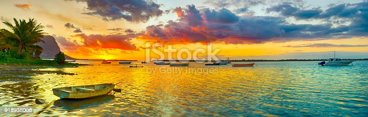 istock Fishing boat at sunset time. Le Morn Brabant on background. Panorama landscape 918938008