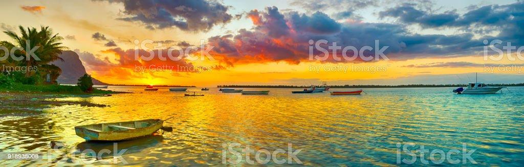 Barco de pesca em vez do sol. Le Morn Brabant em fundo. Paisagem de panorama - foto de acervo