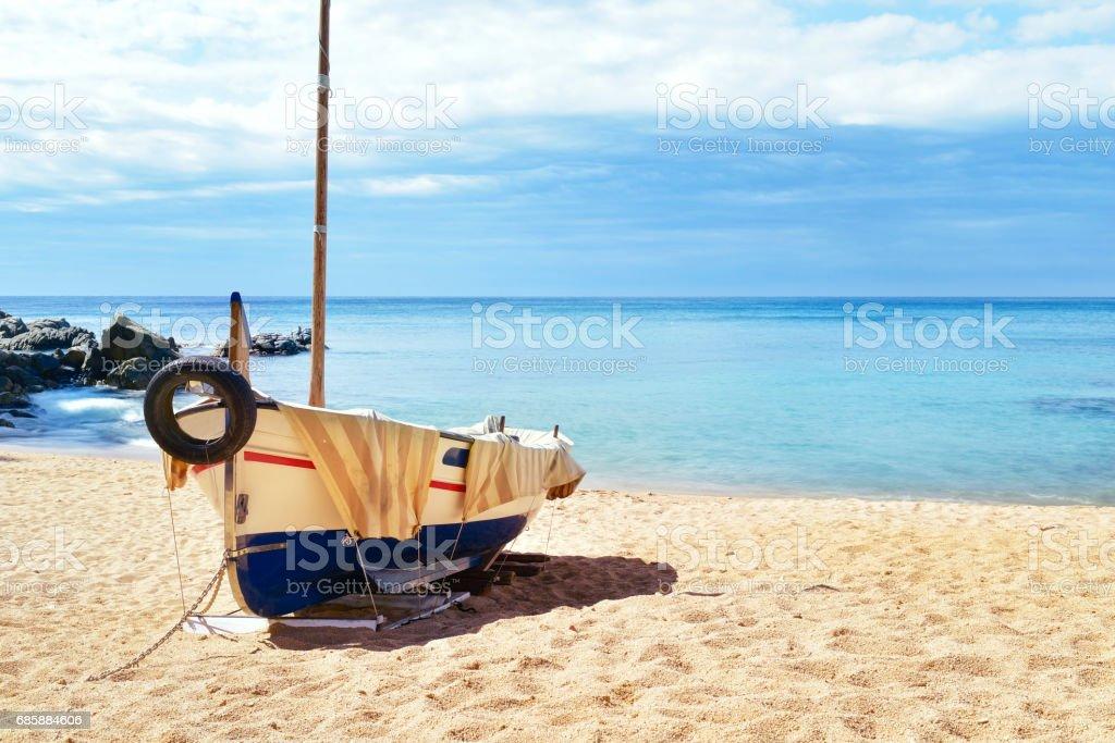 fishing boat beached in Lloret de Mar, Spain an old fishing boat stranded in the quiet beach Platja de Sa Caleta in Lloret de Mar, in the Costa Brava, Spain Beach Stock Photo