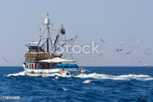 mediterranean style trawler followed by sea gulls