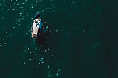 Fishing boat coming back to the harbor in Italy, aerial point of view