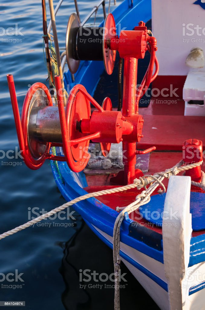Fishing boat detail with red colorful fishing machinery at sunset in Porto Koufo, Sithonia royalty-free stock photo