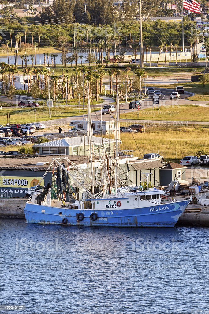 Fishing boat docked next to a fish market royalty-free stock photo