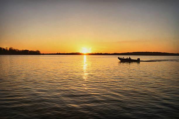 Fishing boat during sunset stock photo