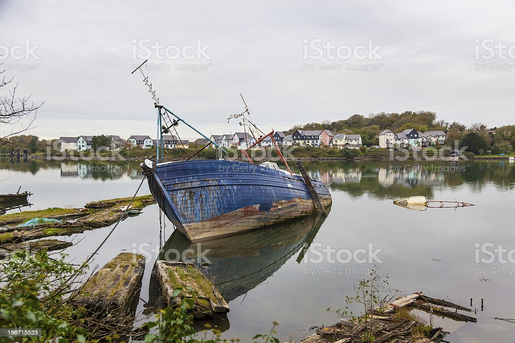 Fishing boat falling apart and sinking in harbour royalty-free stock photo
