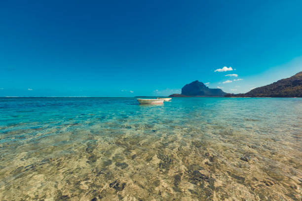 fishing boat in clear water on mauritius island, africa stock photo