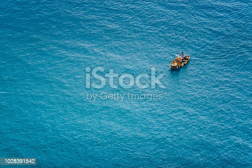 Italy, Liguria, old fishing boat from above in the blue sea
