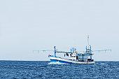 fishing boat in ocean against clear sky.