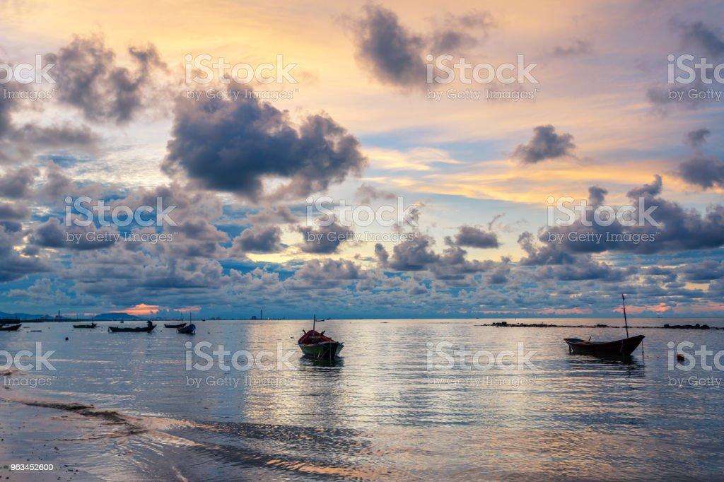 Bateau de pêche en eau de mer parfaitement calme comme du verre avec les nuages dans le ciel, exposition longue prise pendant le lever du soleil - Photo de Bateau à voile libre de droits