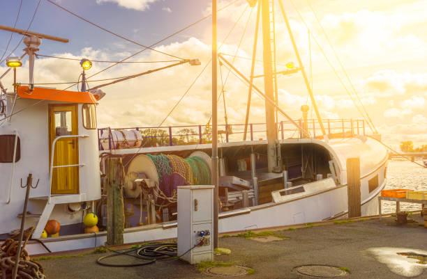 fischerboot im hafen mit hinterleuchteten netzen angeln überfischung - tim siegert stock-fotos und bilder