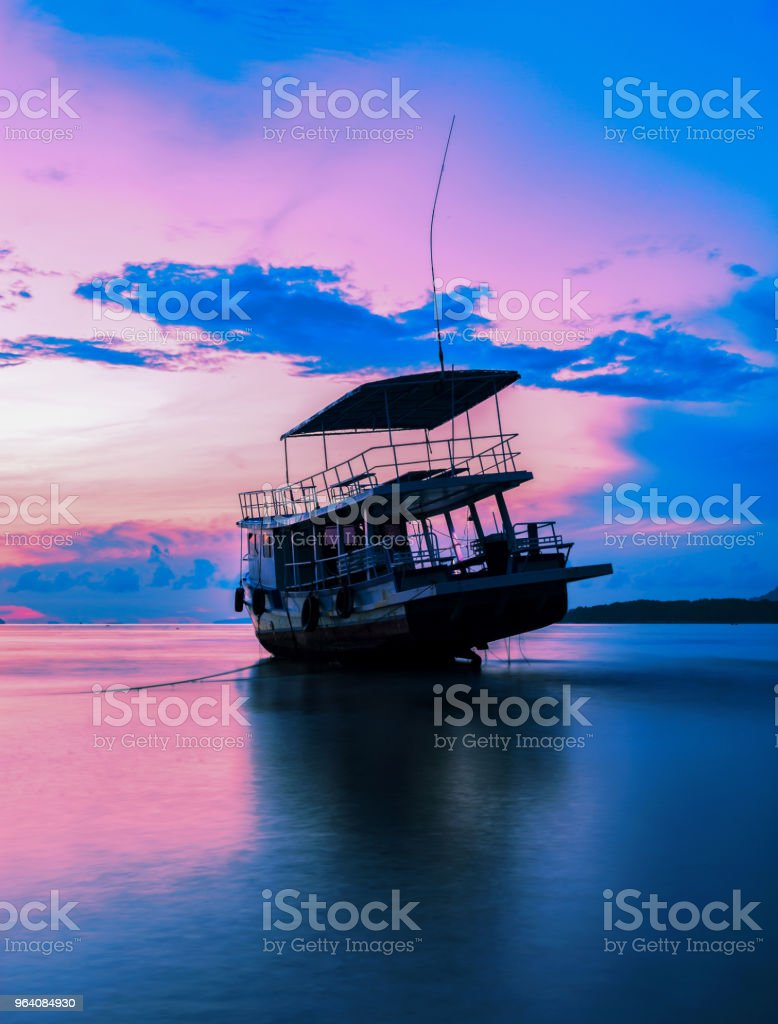fishing boat in the sea in morning time with beautiful sunrise and reflection in the water at phuket andaman sea thailand. - Royalty-free Asia Stock Photo