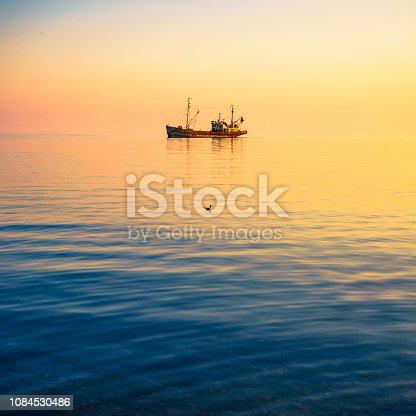 Photo of a fishing boat in the sea with a seagull at sunset.