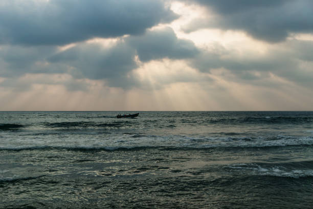 Fishing boat in the waves of the ocean with orange sun rays, Varkala, India stock photo