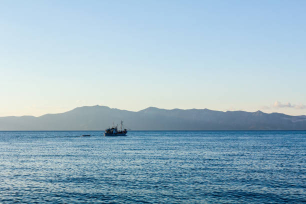 fishing boat is crossing over calm sea - defection stock photos and pictures