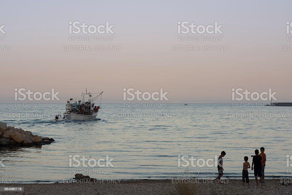 Fishing boat leaves Greek Island harbor at sundown stock photo