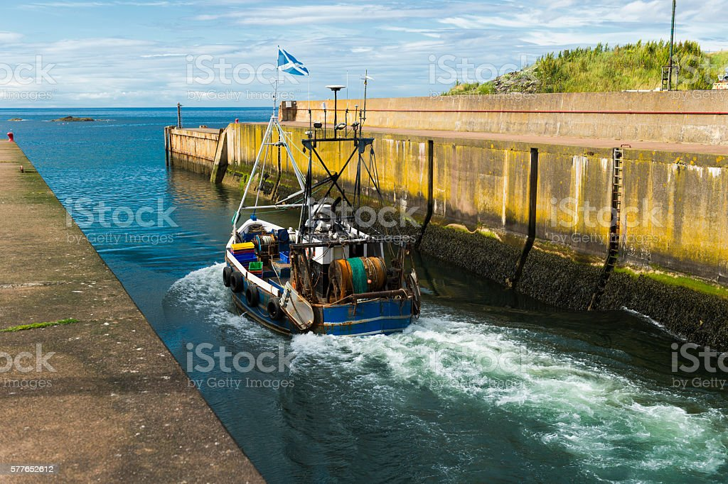 Fishing boat leaving Eyemouth harbour in south east Scotland stock photo