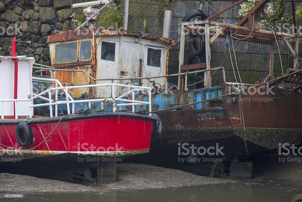 fishing boat lying in  port at low tide stock photo