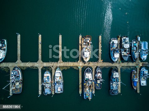 Top down drone shot of a number of fishing boats in a marina on the Washington Coast.
