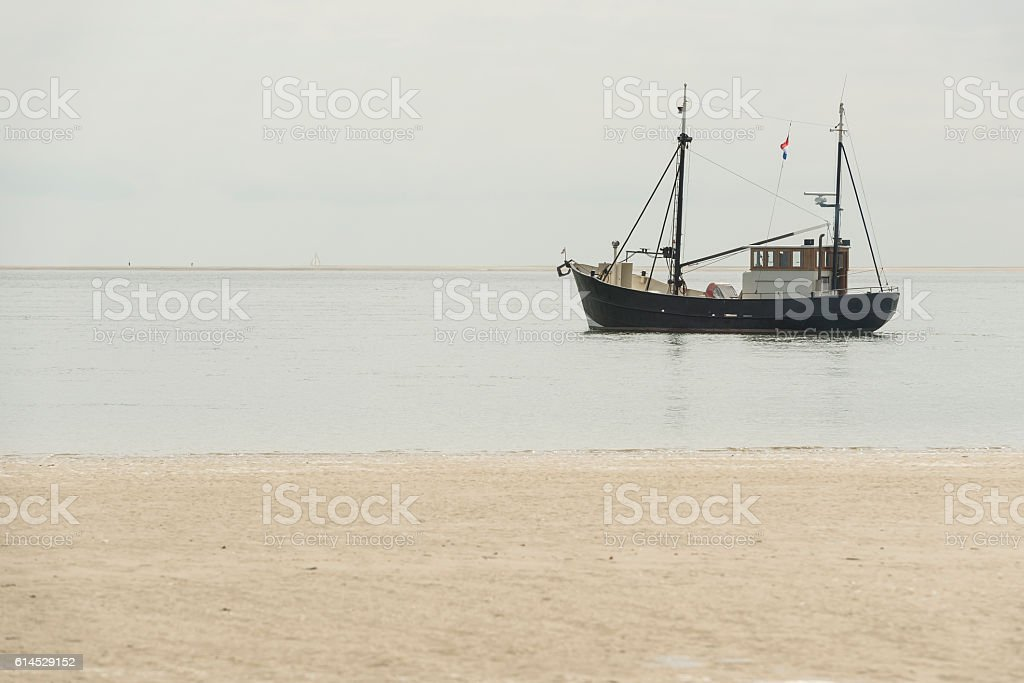 Fishing boat nearby the beach . stock photo