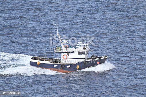 A small fishing boat cruises off the coast of Galicia, northern Spain