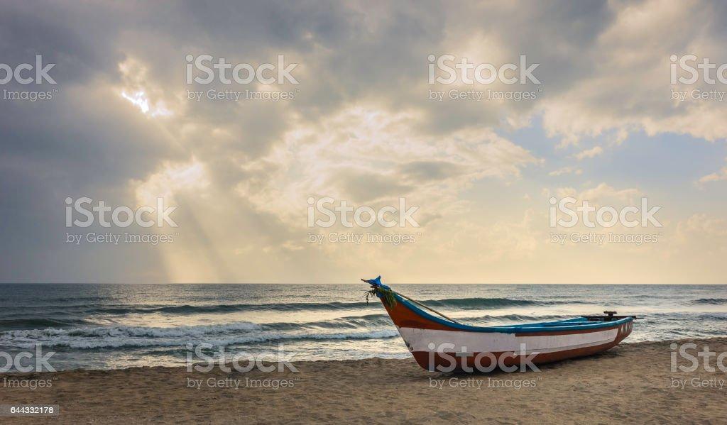 Fishing boat on beach with encroaching monsoon storm in late summer, Mammalapuram, Tamil Nadu, India. stock photo