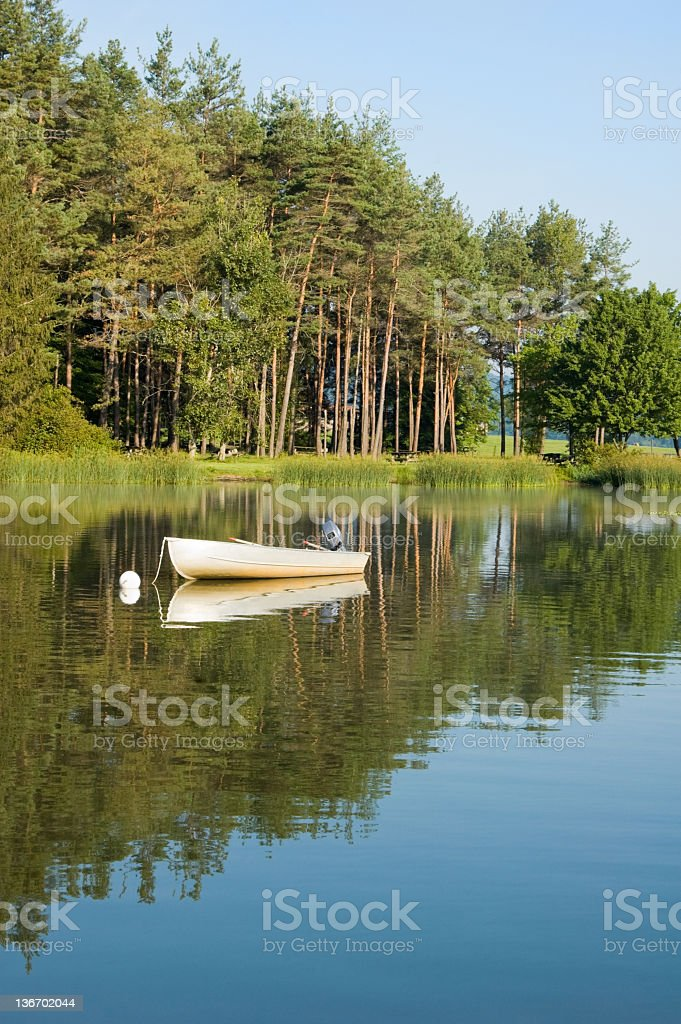 Fishing Boat on Calm Morning Lake in Summer Sunshine royalty-free stock photo