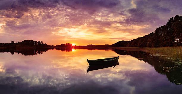 Fishing Boat on Lake during Colorful Sunset - HDR Panorama stock photo