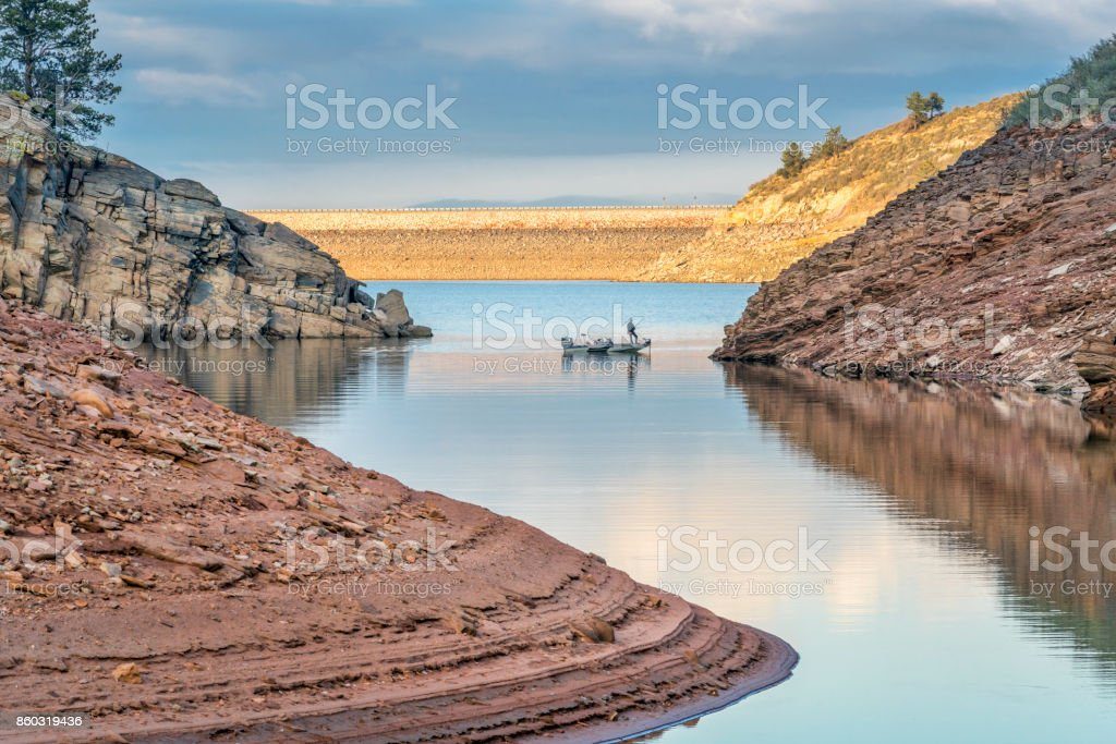 fishing boat on mountain reservoir stock photo
