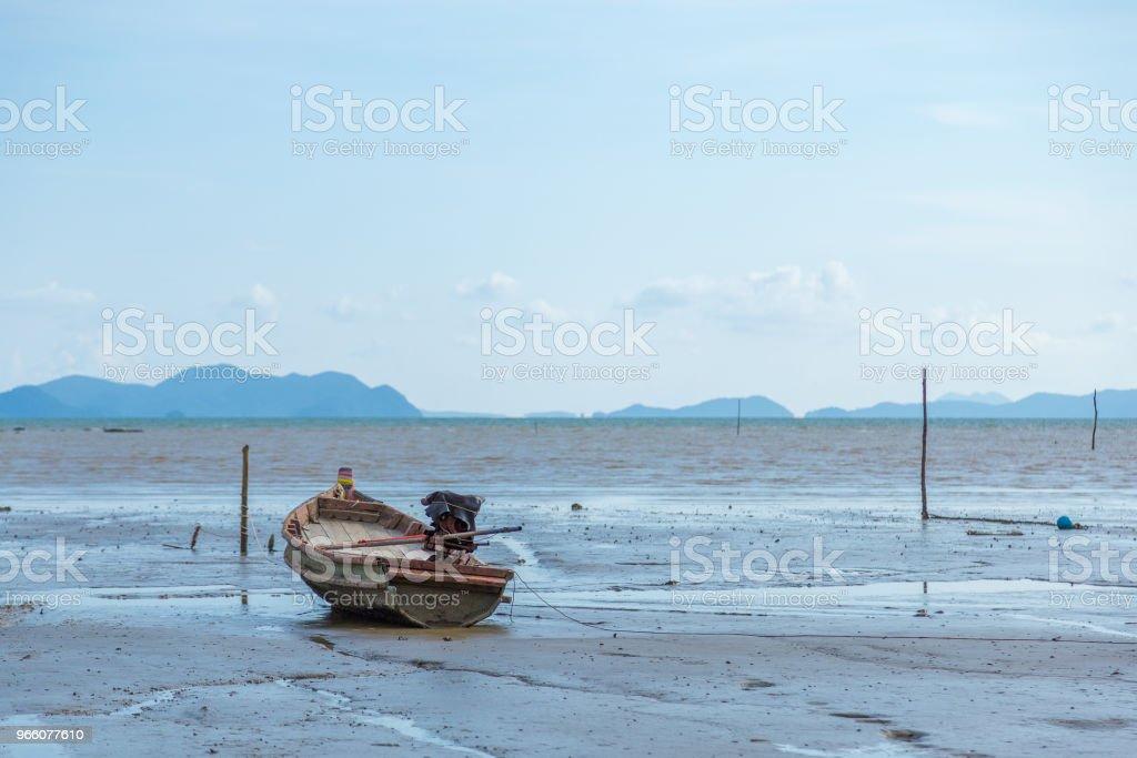 Fiskebåt på stranden vid havet och blå Mountain bakgrund - Royaltyfri Aluminium Bildbanksbilder