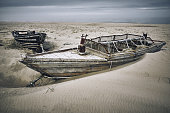 Fishing  lonely wooden boats on the beach sand near the coastline, Sakhalin island, Russia