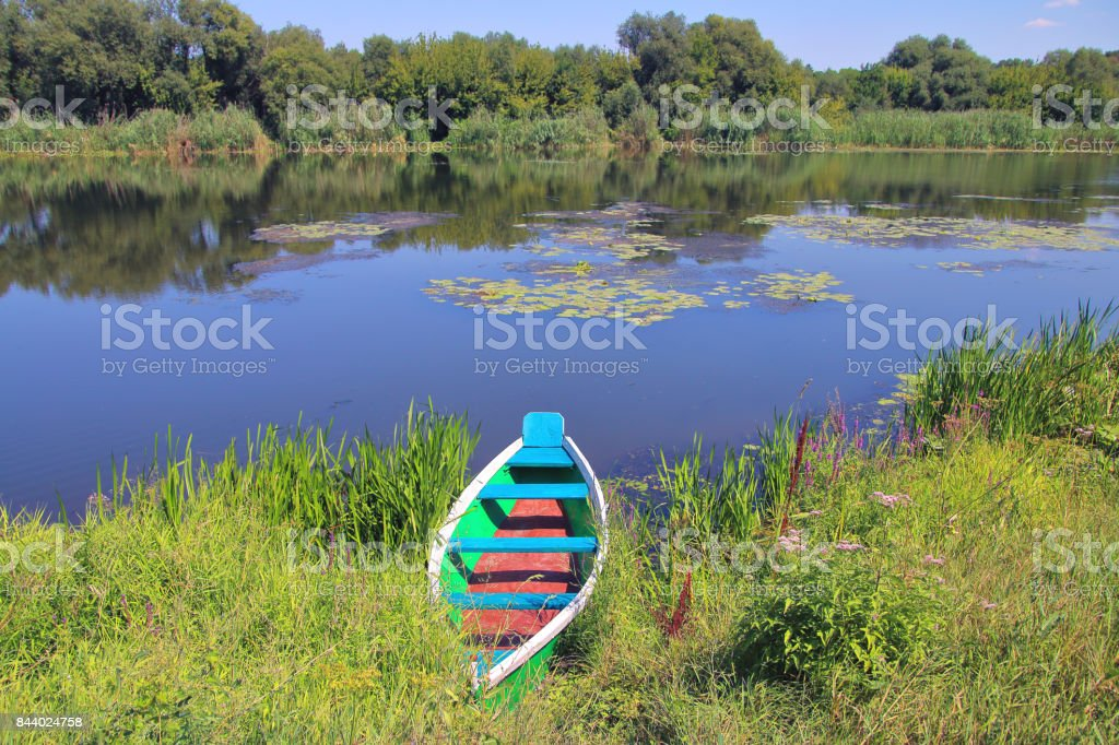 Fishing boat on the picturesque bank of the river. stock photo