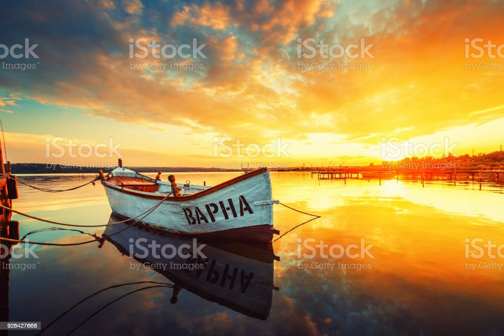 Fishing Boat on Varna lake with a reflection in the water at sunset. stock photo