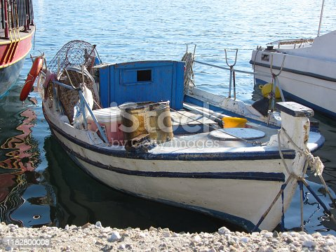 Small fishing boat anchored in marina on a summer day afternoon.