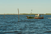 Barra de Caravelas, Brazil - July, 02 2014: A young fisherman steering his small wooden hand made fishing boat and pulling another wooden canoe out of Caravela's Bay at Barra de Caravelas, Caravelas city, Bahia state - Brazil