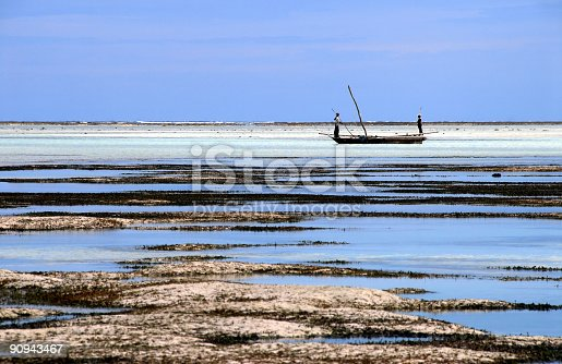 Fishermen coming back at low tide on the east coast of Zanzibar.