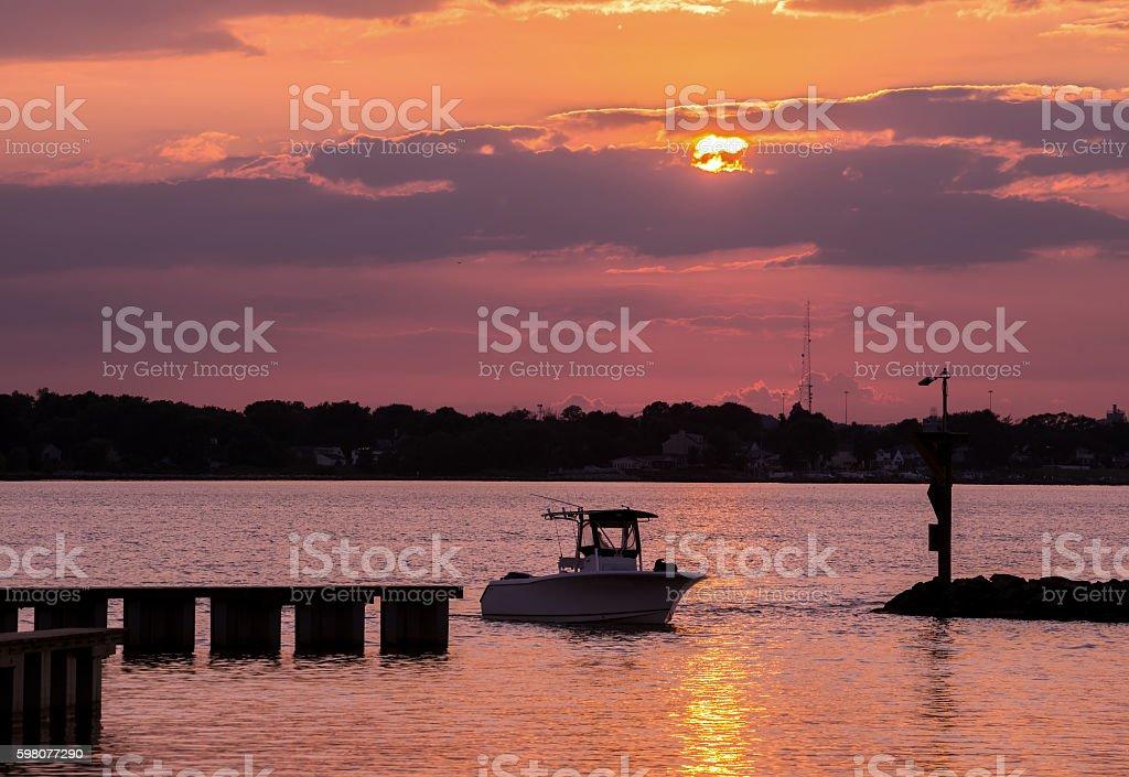 Fishing boat returning home at sunset stock photo