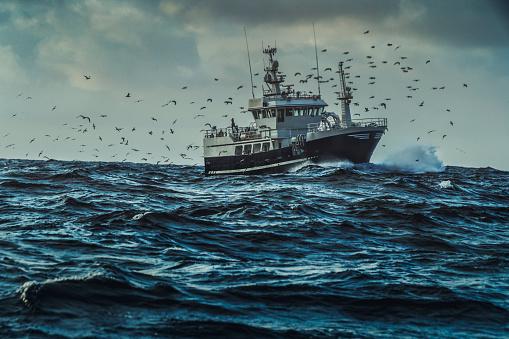 Fishing boat sailing at rough sea