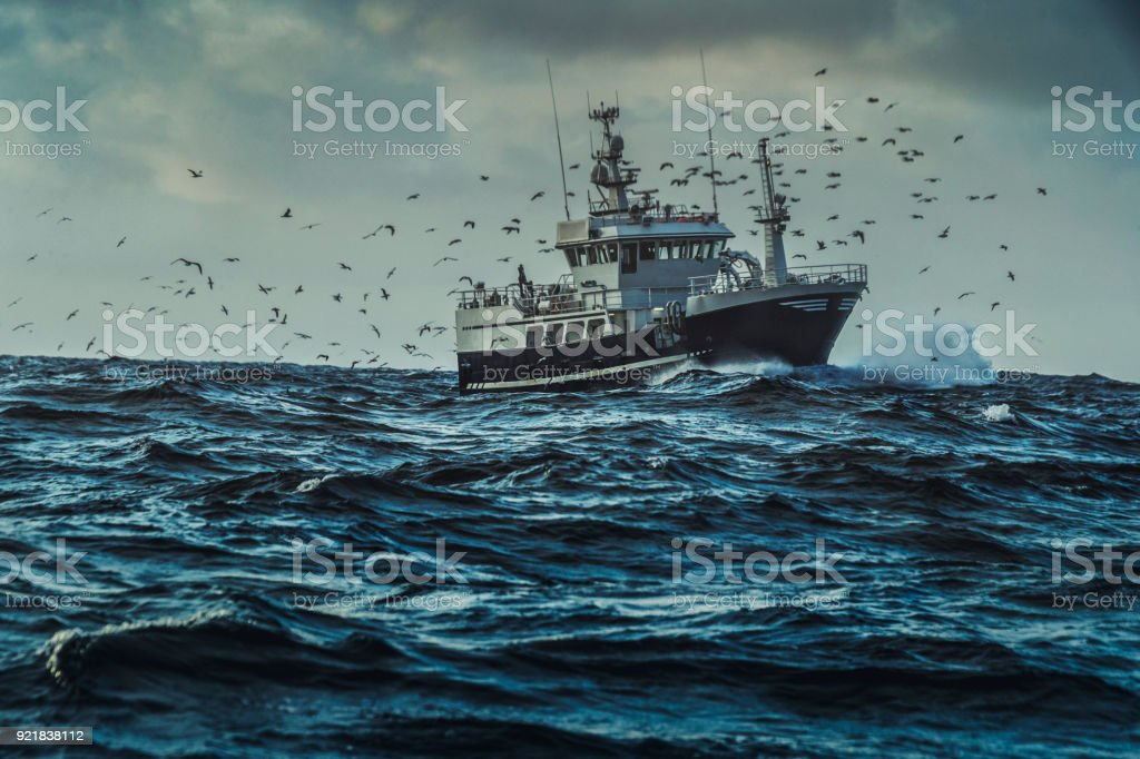 Fishing boat sailing at rough sea stock photo