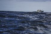 Fishing boat sailing out at rough sea