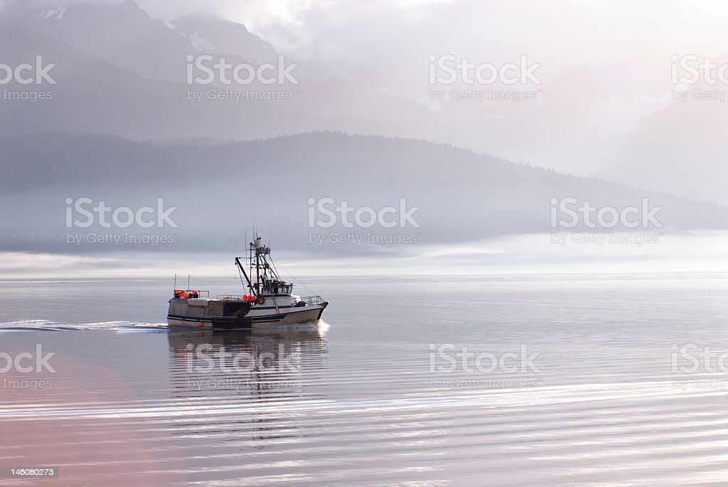 Fishing boat sailing through a landscape with mountains  stock photo