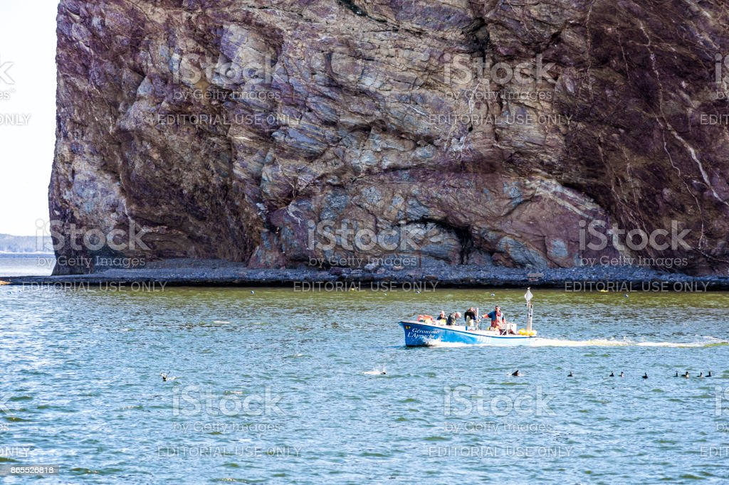Fishing boat with sign swimming by Rocher Perce rock and Bonaventure island in Gaspe Peninsula, Quebec, Gaspesie region stock photo