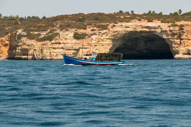 Fishing boat with traditional fish traps off the cliffs and caves in the Algarve, southern Portugal stock photo