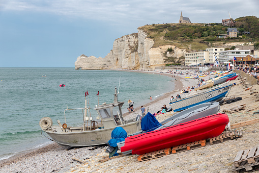 Etretat, France - August 25, 2017: Fishing boats and seaside visitors at beach Etretat, Normandie, France