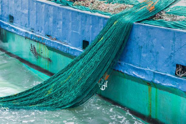 Barcos de pesca y redes de arrastre en el mar - foto de stock