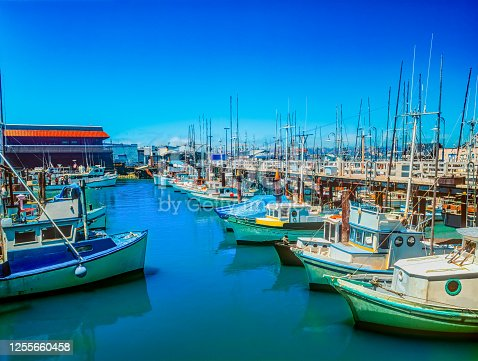 Fishing boats are moored in the water of the San Francisco Bay with the Fisherman's Wharf in the background.