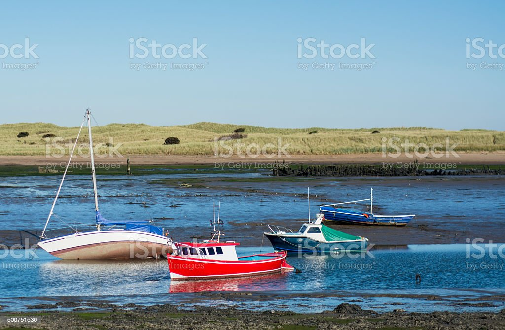 Fishing boats at shore during ow tide stock photo